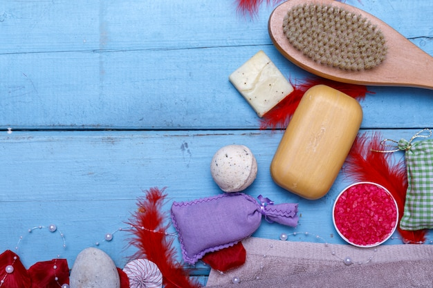 Spa kit or set concept with natural organic products on blue wooden table. soap bar and liquid. aromatherapy pink salt. top view with copy space.