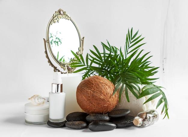 ココナッツ化粧品、禅石、鏡、ヤシの葉、貝殻が入ったspaキット。スパ、美容・健康サロン、化粧品店のコンセプト。白い背景の上の写真を閉じる