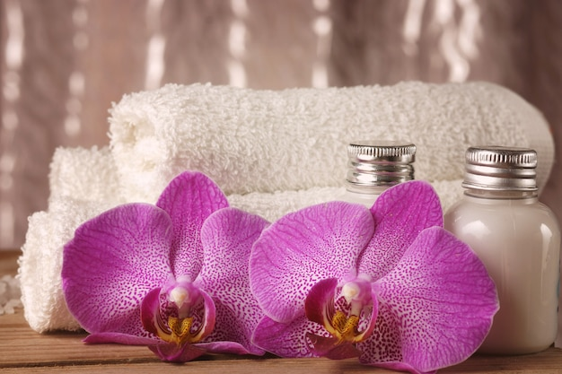 Spa kit with lotions for skin, orchid flowers and white towels