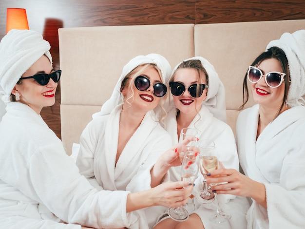 スパの余暇。 bffリラクゼーション。サングラス、バスローブ、タオルターバン。シャンパンをチリンと鳴らす女性。乾杯。
