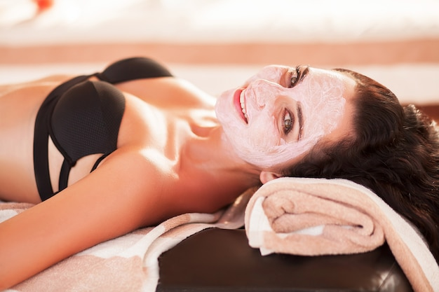 Spa mask. beautiful woman get spa mask on the sunny beach in spa salon outdoor. high quality. scin care.
