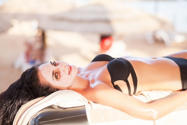 Spa mask, beautiful woman get spa mask on the sunny beach in spa salon outdoor