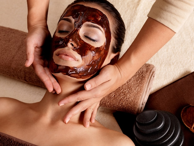 Спа-массаж для молодой женщины с лицевой маской на лице - в помещении
