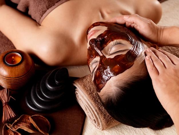 顔にフェイシャルマスクを付けた若い女性のためのスパマッサージ-屋内