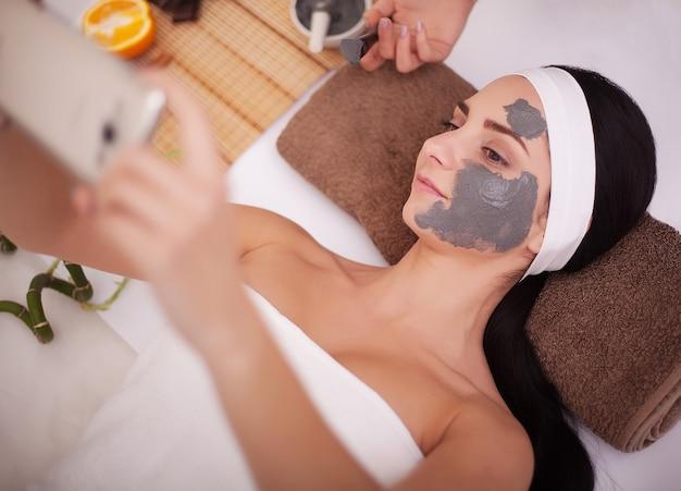 Спа-массаж для молодой женщины с маской для лица на лице