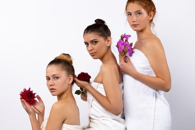 스파 모델 여성은 흰 수건에 싸여 있고 흰 벽에 피라미드 형태로 포즈를 취하는 천연 꽃을 들고 있습니다.