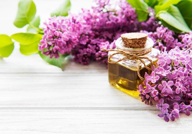 Спа-масло с цветами сирени. бутылка с ароматическим маслом и цветами сирени на деревянной поверхности.
