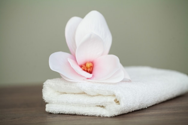 Spa orchid with soft towels on wooden table.