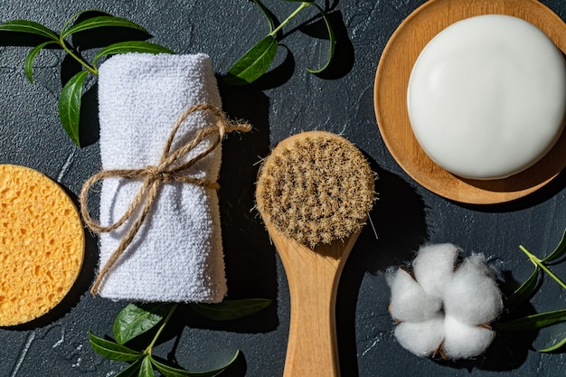 Spa organic natural accessories for face and body treatment with cotton flower and green leaves on black background. zero waste bathroom essentials, plastic free items.