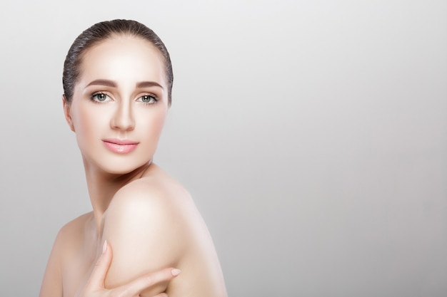 Spa portrait of beautiful woman on grey background closeup. girl with clean skin