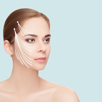 파란색 배경 위에 그녀의 얼굴에 화살표가있는 매력적인 여자의 스파 초상화. 얼굴 리프팅 개념. 성형 외과 치료, 의학