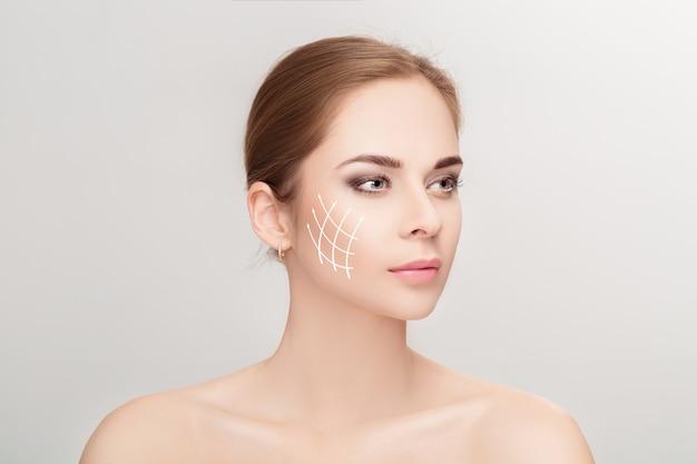 회색 배경 위에 그녀의 얼굴에 화살표가있는 매력적인 여자의 스파 초상화. 얼굴 리프팅 개념. 성형 외과 치료, 의학