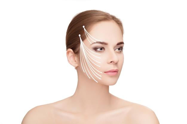 흰색 배경 위에 그녀의 얼굴에 화살표가있는 매력적인 여자의 스파 초상화. 얼굴 리프팅 개념. 성형 외과 치료, 의학