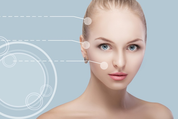 Spa portrait of young and natural woman with dotted arrows on face on blue background. medicine and skin care