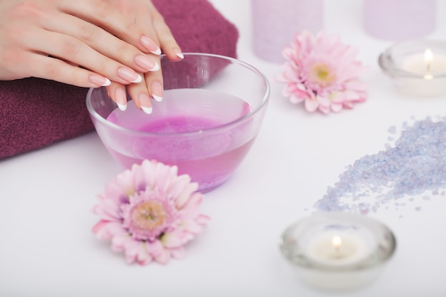 Spa procedure, woman in beauty salon holding fingers in aroma bath for hands