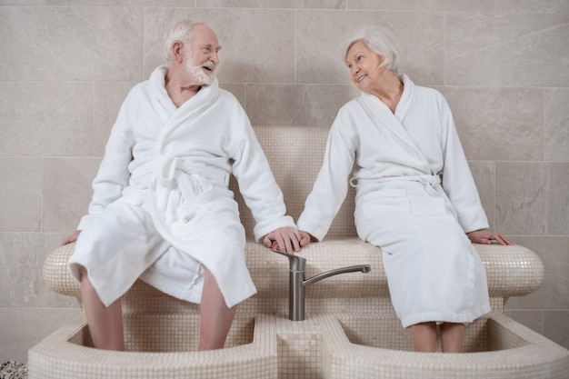 스파 절차. 흰색 가운에 성숙한 부부는 발에 대한 수압 마사지를하고 좋은 느낌