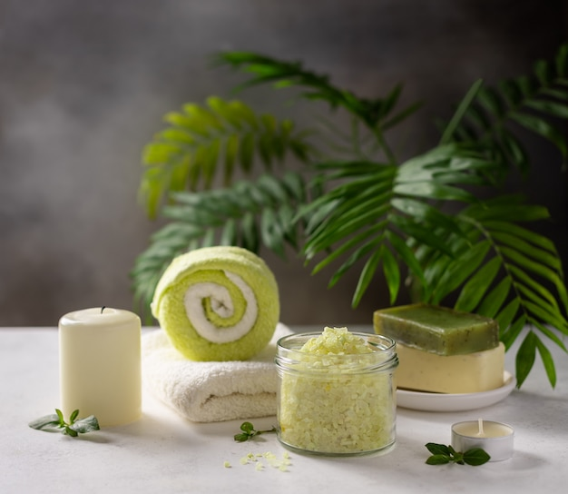 Spa product composition with sea salt, solid soap, candles and bath towels on a background of green palm leaves spa wellness relax concept