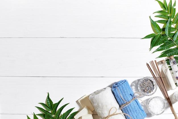 スパ製品バスソルトドライフラワーラベンダー石鹸キャンドルとタオルフラットは白い木製の背景に横たわっていた