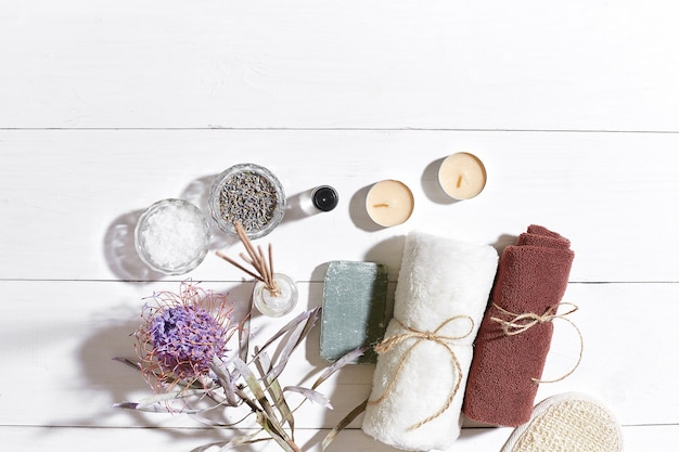 Spa products bath salts dry flowers lavender soap candles and towel flat lay on white wooden backgro