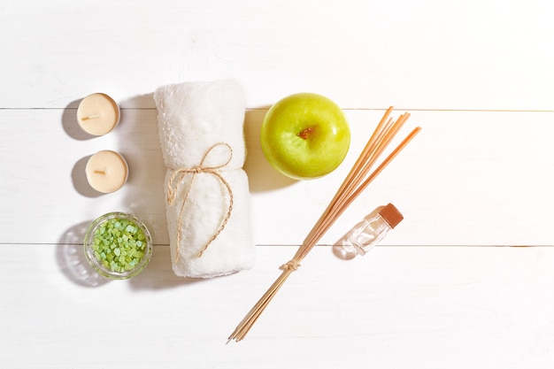 Spa products bath salts soap candles and towel flat lay on white wooden background top view sun flare
