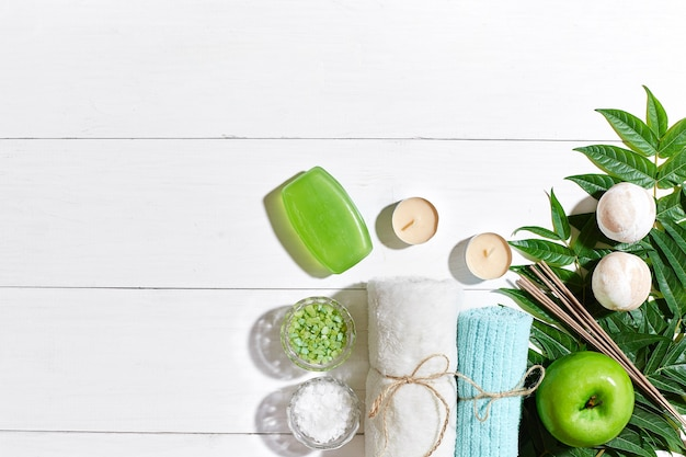 Spa products bath salts soap candles and towel flat lay on white wooden background top view