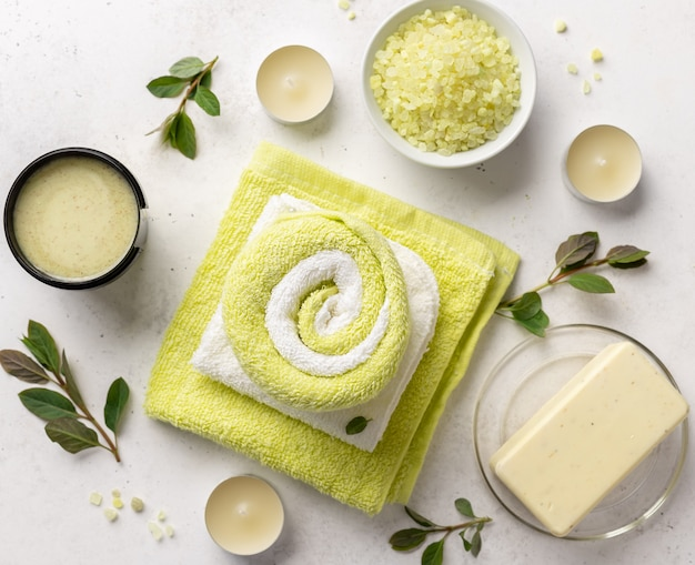 Spa products composition with sea salt, scrub, soap and bath towels on a white stone background with candles and green leaves , close-up