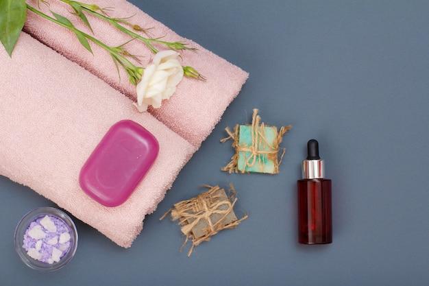 페이셜 및 바디 케어용 스파 제품. 천연 바다 소금, 수제 비누, 아로마 오일 한 병, 회색 배경에 꽃이 있는 분홍색 수건. 스파 및 바디 케어 개념입니다. 평면도.