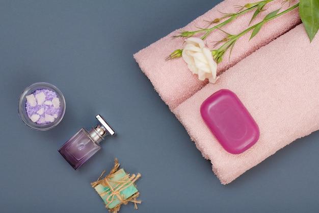 페이셜 및 바디 케어용 스파 제품. 천연 바다 소금, 수제 비누, 향수, 회색 배경에 꽃이 있는 분홍색 수건. 스파 및 바디 케어 개념입니다. 평면도.