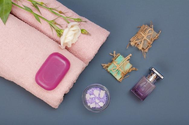 페이셜 및 바디 케어용 스파 제품. 천연 바다 소금, 수제 비누, 향수, 분홍색 수건, 회색 배경에 꽃이 있습니다. 스파 및 바디 케어 개념입니다. 평면도.