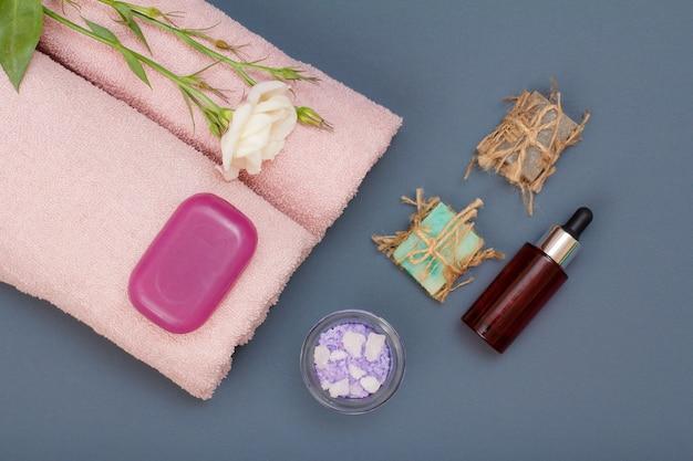마사지, 페이셜 및 바디 케어를 위한 스파 제품. 천연 바다 소금, 수제 비누, 아로마 오일 한 병, 회색 배경에 꽃이 달린 분홍색 수건. 스파 및 바디 케어 개념입니다. 평면도.