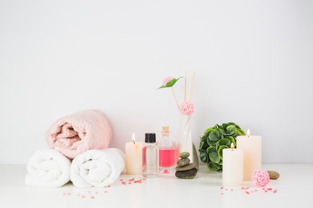 Spa products and illuminated candles on white tabletop