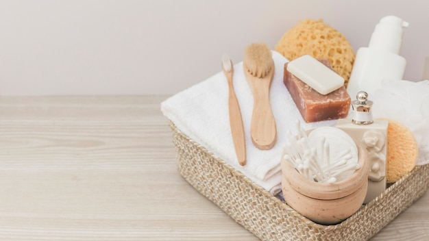 Spa products with brushes and loofah in tray on wooden backdrop