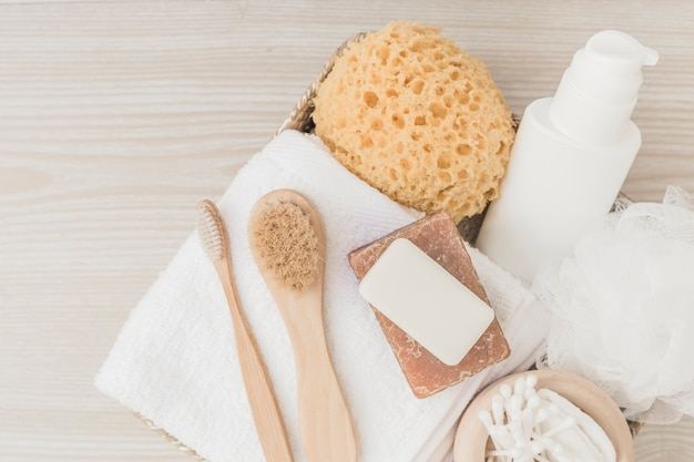 Spa products with brushes and loofah on wooden background