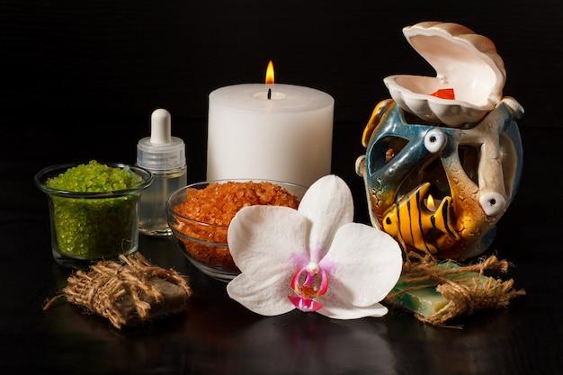 난초 꽃, 수제 비누, 바다 소금이 든 그릇, 아로마 오일이 든 병, 검은 배경에 촛불이 있는 스파 제품