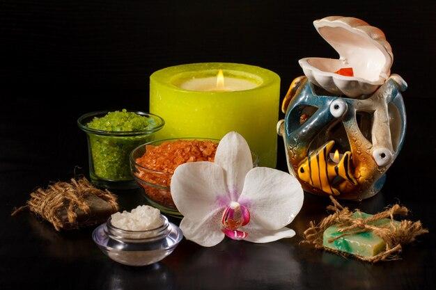흰색 난초 꽃이 있는 스파 제품, 수제 비누, 바다 소금이 든 그릇, 검정색 배경에 촛불