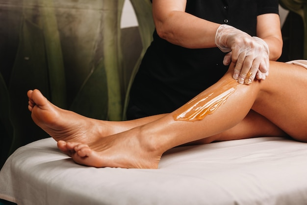 Spa professional having a sugaring session on legs for a charming woman