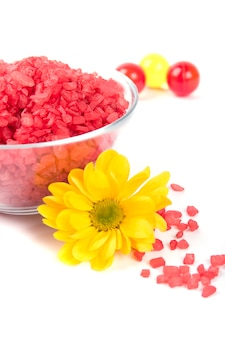 Spa pruducts: bath salt, oil balls in a bowl and yellow flower