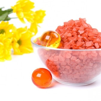 Spa pruducts: bath salt, oil balls in a bowl and yellow flowers