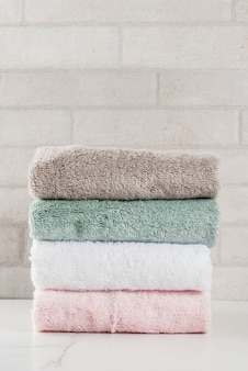 Spa relax and bath concept, stack clean bath towels colorful cotton terry textile in bathroom white surface top view