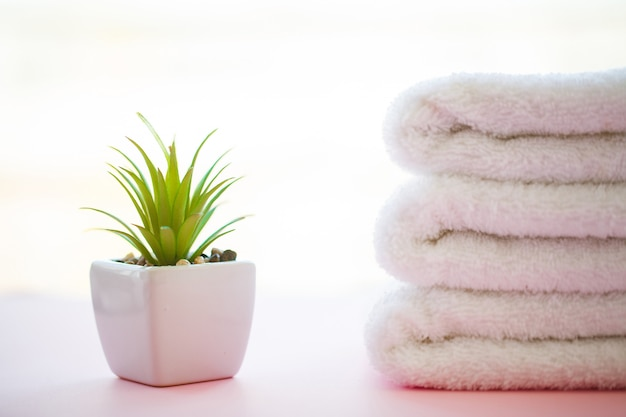 Spa relax and bath concept, stack clean bath towels colorful cotton terry textile in bathroom