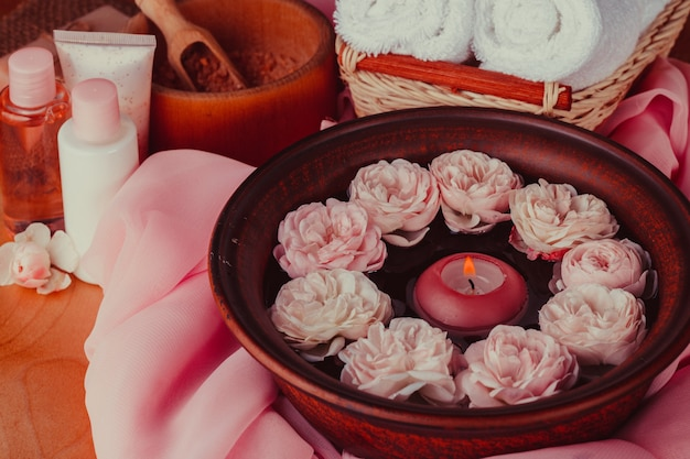 Spa relaxation - burned candle floating in rose water