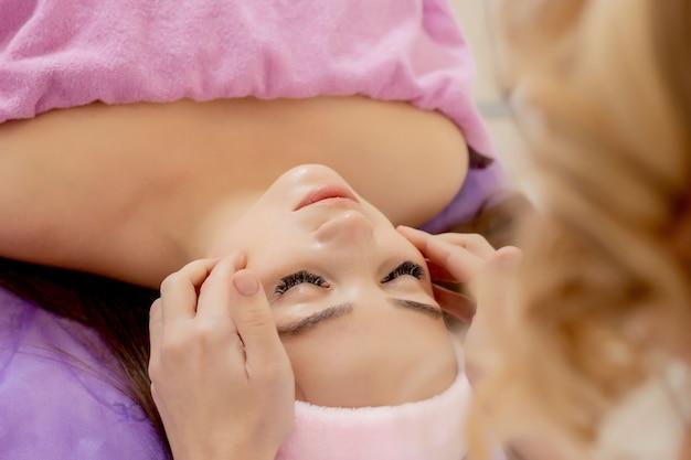 스파, 리조트, 미용 및 건강 개념 - 스파 살롱에서 얼굴 치료를 받는 아름다운 여성.