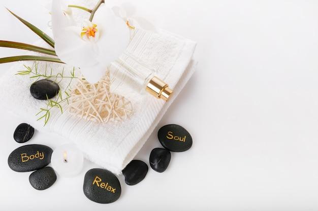 Состав санаторно-курортной терапии. горящие свечи, черные камни, полотенце, орхидея, абстрактные огни на белом. валентина спа-концепция
