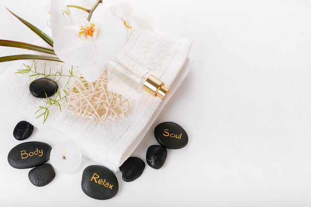 Spa resort therapy composition. burning candles, black stones, towel, orchid, abstract lights on white . valentines spa concept