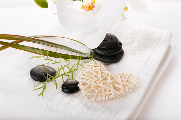 Spa resort therapy composition. burning candles, stones, towel, orchid abstract lights