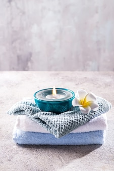 Spa resort therapy composition. burning candles, towel and flower on a stone , copyspace