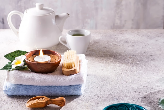 Spa resort therapy composition. burning candles, towel, tea set and flower on a stone , copyspace