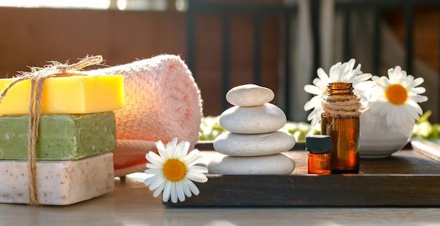 スパセット。カモミールの花、ボディオイル、オーガニック石鹸、タオルはリラックスと健康のコマーシャルに最適です。