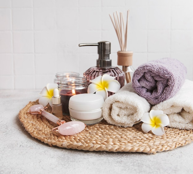 Spa set, essential oil, massage salt, candle and  frangipani flowers on gray concrete background