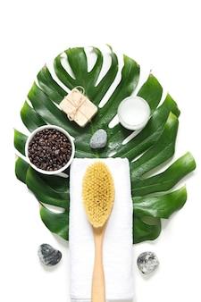 Спа набор для снятия целлюлита, жесткая кисть cacius, кофейные зерна, мыло, полотенце, декорированный лист монстера. вид сверху. вертикальный формат.